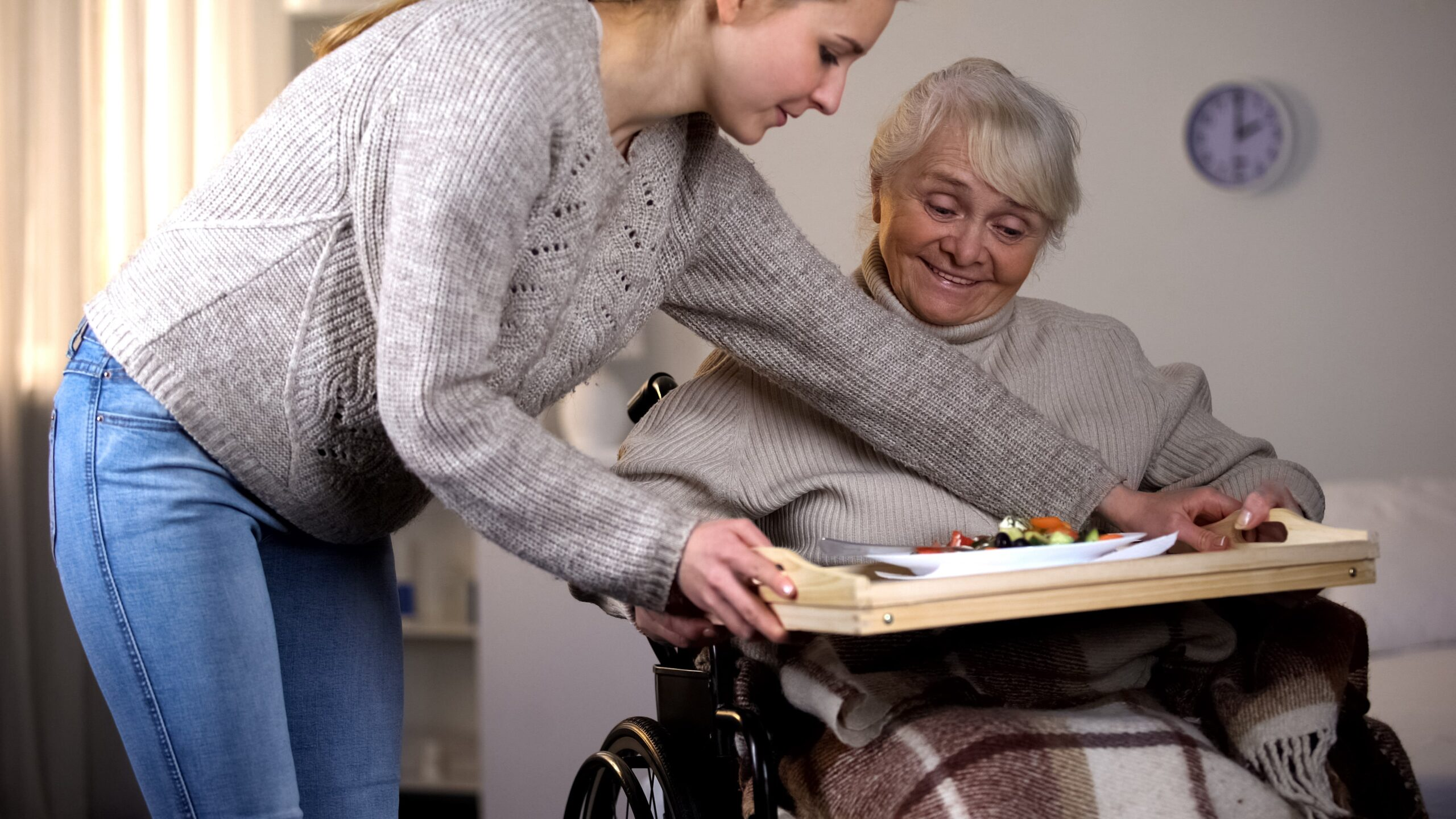 a nurse serving food to a old woman